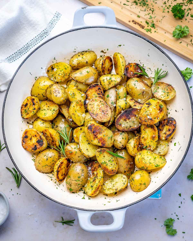 cartofi noi rumeniti in tigaie cu verdeturi pe deasupra
