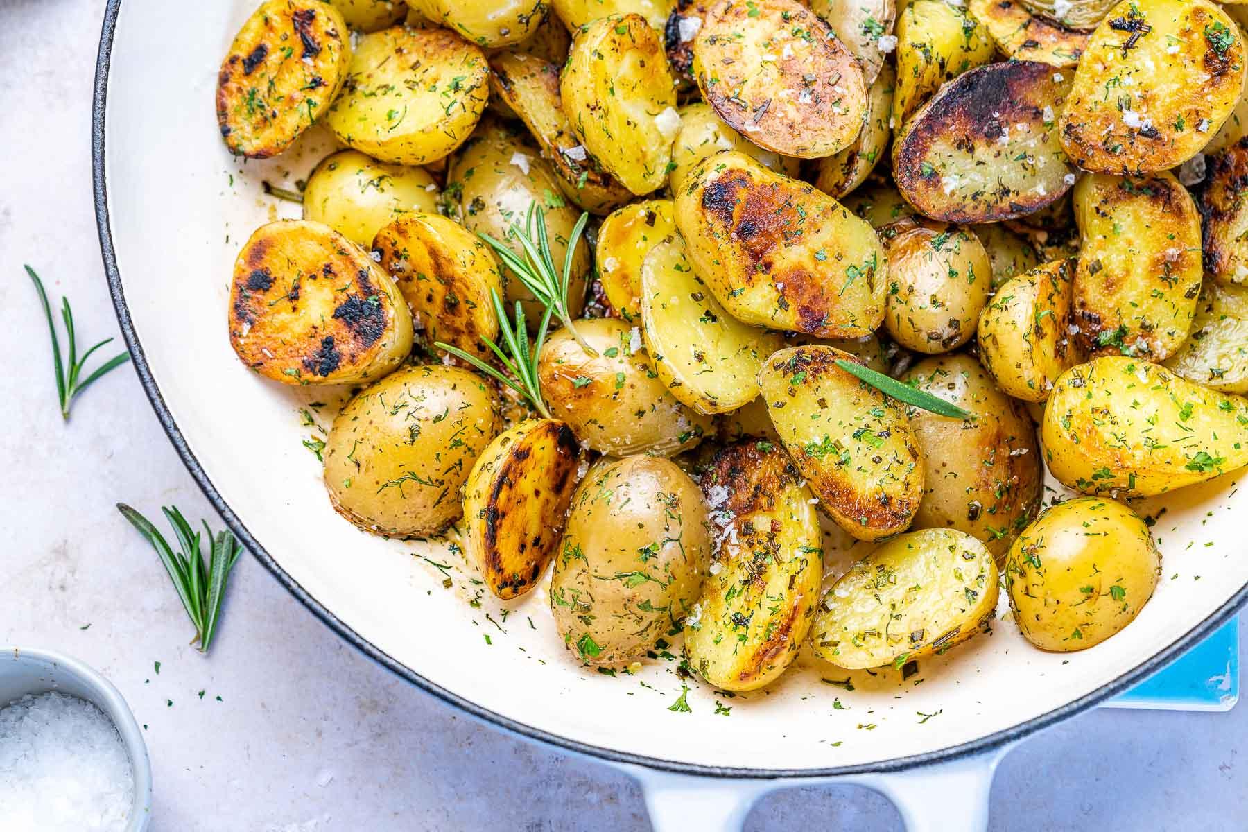 cartofi inabusiti in tigaie cu usturoi si verdeturi si sare deasupra