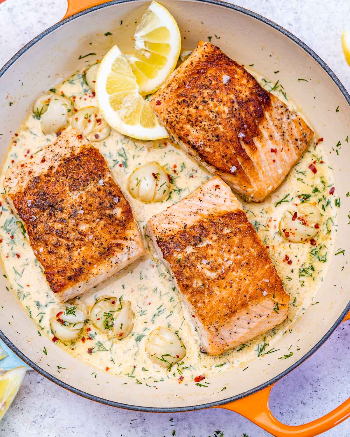 skillet with three salmon fillets in cream sauce