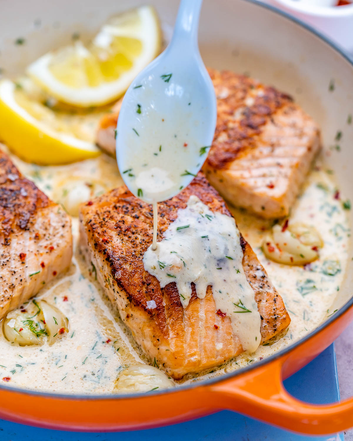 pouring sauce over salmon fillets in a skillet with lemon slices